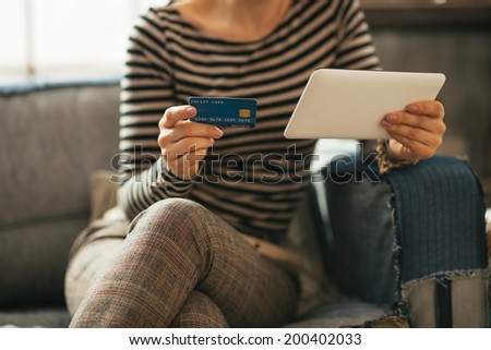 Closeup on young woman with credit card and tablet pc sitting on divan - stock photo