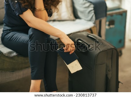 Closeup on young woman with passport, ticket and luggage - stock photo