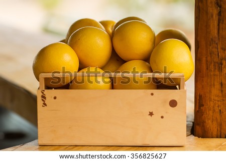 Closeup one timber lug-box full of clean organic natural fresh tasty ripe yellow grapefruits crop fruit full of vitamin for healthy eating diet on light blurred background, horizontal picture - stock photo