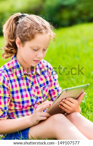 Closeup outdoor portrait of a pretty  teenager girl in casual clothes sitting on the grass in sunlight with digital tablet in her hands - stock photo