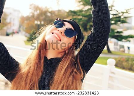 Closeup outdoors shot of pretty smiling young female tourist takes selfie. Caucasian woman wearing retro sunglasses and black hat.  - stock photo