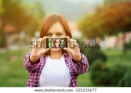 Closeup outdoors shot of young redhead Caucasian woman taking a selfie in park in autumn. Cute casual girl taking a self portrait with smartphone outdoors in fall. - stock photo