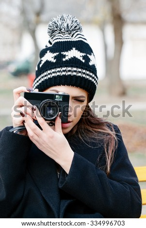Closeup outside portrait of beautiful brunette girl taking photo with camera in her hands. Wearing cozy knitted beanie and  jacket. Nature background - stock photo