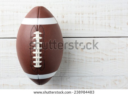 Closeup overhead shot of an American collegiate style football on a whitewashed wood table. The ball is offset ot the left with copy space on the left side of the image. - stock photo