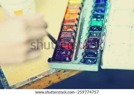 Closeup paintbrush artist drawing watercolor, dunks brush in the paint, selective focus - stock photo