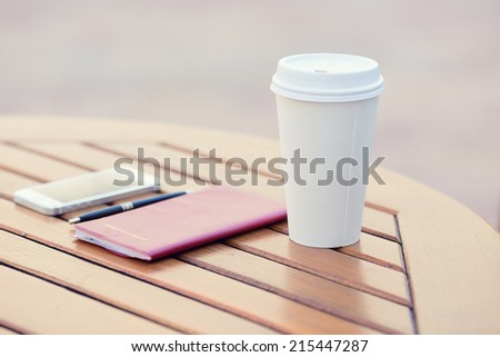 Closeup paper coffee cup, weekly organizer, planning book, smartphone, pen on table of city cafe, outside on sunny day. Life, accessories of corporate businessperson - stock photo