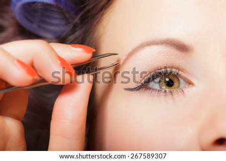 Closeup part of face, woman plucking eyebrows depilating with tweezers. Girl tweezing eyebrows. - stock photo
