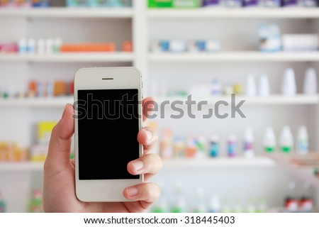 closeup pharmacist hand holding smart phone with blur some shelves of drug in the pharmacy drugstore - stock photo