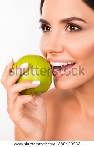 Closeup photo of a beautiful healthy girl biting an apple - stock photo