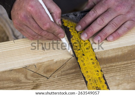 Closeup photo of a carpenter using scale and pencil to mark on the wood. - stock photo