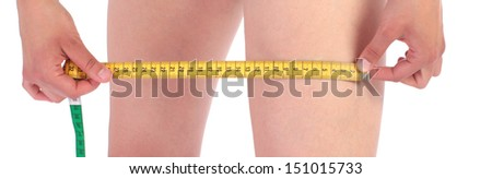 Closeup photo of a Caucasian woman's leg. She is measuring her thigh with a yellow metric tape measure after a diet. - stock photo
