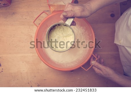Closeup photo of a chef lady sifting flour for kneading. Retro colors, directly above - stock photo