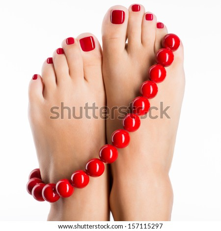 Closeup photo of a female feet with beautiful red pedicure and big beads -  over white background - stock photo