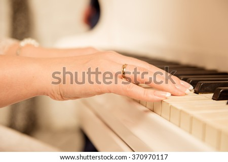 Closeup photo of a female musician playing the piano - stock photo