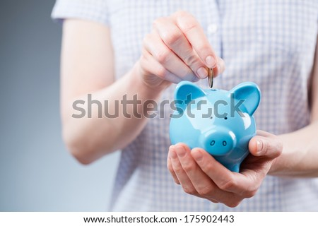 Closeup photo of a young person putting a one dollar coin into a blue piggy bank. - stock photo