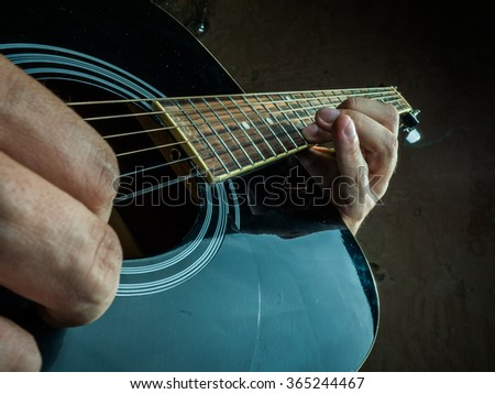 Closeup photo of an acoustic guitar played by a man. Only hands visible. Unrecognizible guitar player. - stock photo