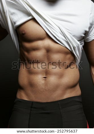 Closeup photo of an athletic guy with perfect abs - stock photo