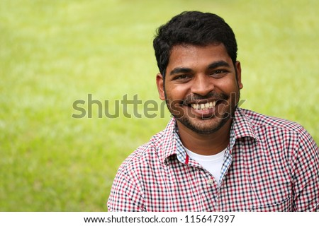 Closeup photo of attractive, handsome & smart south-asian/indian entrepreneur with smiling expression. The person is wearing a formal shirt & the picture is shot with beautiful lawn in the background - stock photo
