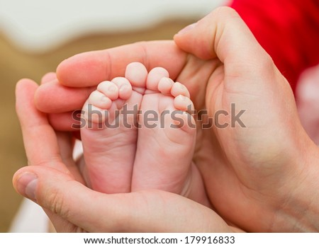 Closeup photo of baby foots in father hands - stock photo