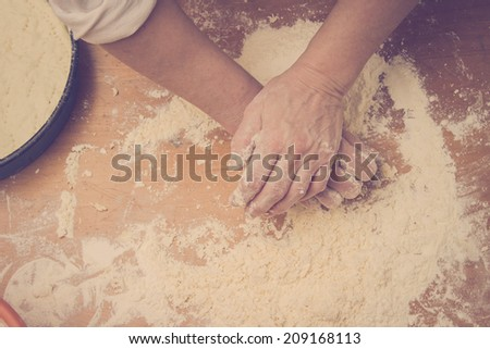 Closeup photo of baker making dough for bread. Retro styled imagery - stock photo