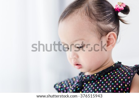 Closeup photo of beautiful cute asian baby's expression at home. - stock photo