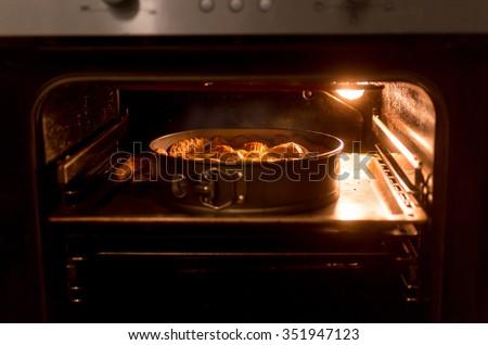 Closeup photo of big apple pie baking in hot oven - stock photo