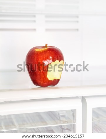 Closeup photo of big red bitten apple in the empty fridge, fruits diet, healthy lifestyle, organic nutrition, weight lost concept - stock photo