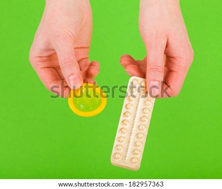 Closeup photo of birth control pills and condom holding in hands - stock photo