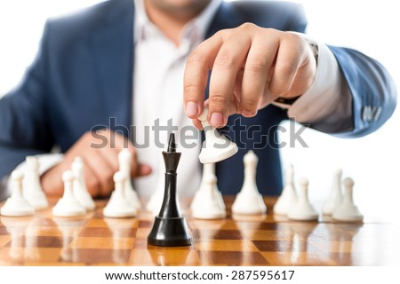 Closeup photo of businessman playing chess and beating black king - stock photo