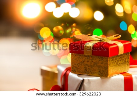 Closeup photo of Christmas gift boxes on the background of lights - stock photo