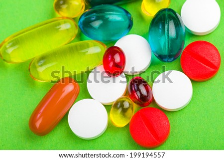 Closeup photo of colorful pills on green isolated background - stock photo