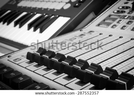closeup photo of digital studio mixer fader & keyboard synthesizer. black and white processed for music background - stock photo
