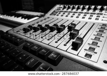 closeup photo of digital studio mixer fader & keyboard synthesizer. black and white processed for recording or radio / tv broadcast background - stock photo
