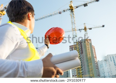 Closeup photo of engineer posing on building site with orange hardhat - stock photo