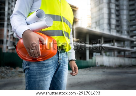 Closeup photo of engineer with hardhat and blueprints posing on building site - stock photo
