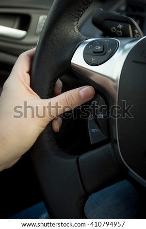 Closeup photo of female driver adjusting cruise control system on steering wheel - stock photo