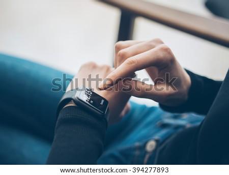 Closeup photo of female hand touching screen generic design smart watch. Film effects, blurred background. Horizontal - stock photo
