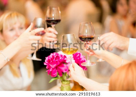 Closeup photo of hands clinking glasses with red and white wine - stock photo
