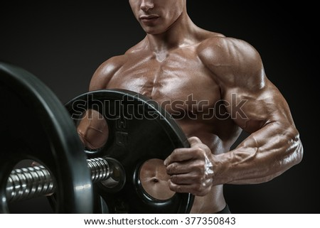 Closeup photo of handsome bodybuilder guy prepare to do exercises with barbell in a gym, keep barbell plate in hands - stock photo