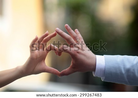 Closeup photo of happy married couple making heart with hands and fingers outside, horizontal picture - stock photo