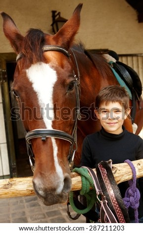 Closeup photo of little boy and horse standing, boy smiling, looking at camera. - stock photo