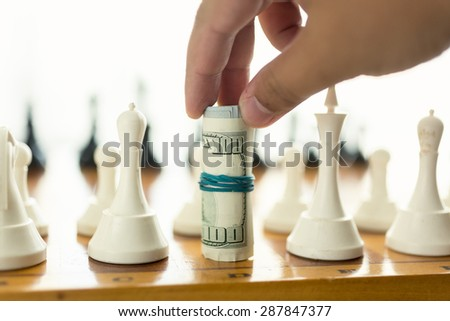 Closeup photo of man making move in chess game with twisted banknotes - stock photo