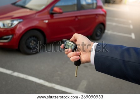 Closeup photo of man pressing the button on remote car alarm system - stock photo