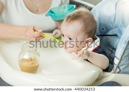 Closeup photo of 9 months old baby boy eating fruit sauce from glass jar - stock photo