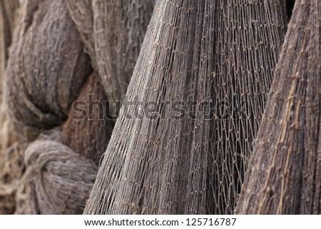 Closeup photo of old gray fishing nets. Outdoors, daylight. - stock photo