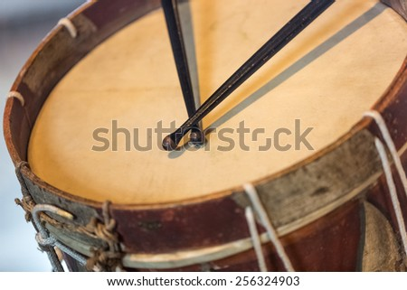 Closeup photo of old military drum with black sticks - stock photo