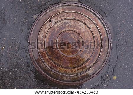 Closeup photo of Old Sewer rust manhole cover on the urban asphalt road. Rain scene - stock photo