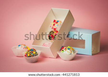 Closeup photo of open box with homemade cake balls with colorful sprinkles over pink background - stock photo