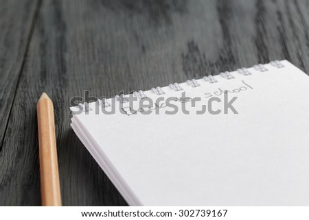 closeup photo of open empty notepad with back to school phrase, on wood table - stock photo