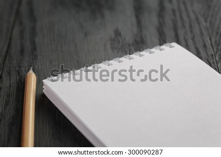 closeup photo of open empty notepad with pencil, on wood table - stock photo